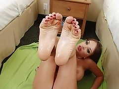 Hot brunette gives an expert footjob to horny stud