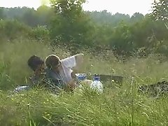 A guy lets a hot chick blow him out in the middle of a field
